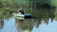 The fisherman floats on the river in an inflatable boat. Early morning with fog Stock Footage