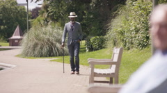 4K Senior man walking with stick in the park & other senior gents relaxing Stock Footage