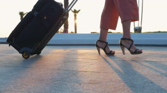 Young business lady walking with suitcase at the seafront at sunrise, close up Stock Footage