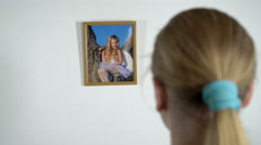 Young girl looking at photograph of a little girl in photo frame on the wall Stock Footage