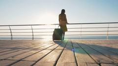 Young business lady with suitcase at the seafront during sunset or sunrise,dolly Stock Footage