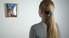 Young girl staring at photo of a little girl in frame hanging on the wall Stock Footage