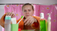 Teenage girl in bathrobe brushing her teeth in bathroom looking in the mirror Stock Footage