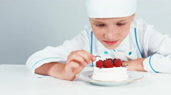 Close up portrait little chef cook decorating chocolate shavings cake Stock Footage