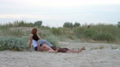 A young couple in love lies on a wild sea beach at sunset and hugging. Stock Footage