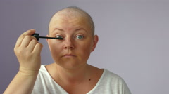 Hairless woman ill with cancer is doing her makeup in front of a mirror Stock Footage