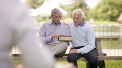 4K Senior male friends relaxing in the park & looking at tablet computer Stock Footage