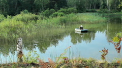 The fisherman floats on the river in an inflatable boat. Moving camera by slider Stock Footage