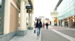 Blurred brunette girl in high heels walking with shopping bags by outlet fashion Stock Footage