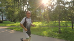 The man likes to run in the park, for a healthy lifestyle Stock Footage