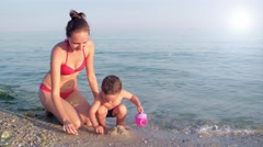 Baby and mother are building castles in the sand Stock Footage
