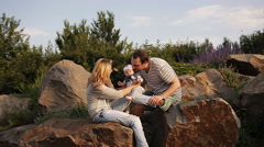Young parents with a daughter play in the park at sunset Stock Footage