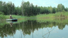 The fisherman floats on the river in an inflatable boat. Moving camera by slider - stock footage