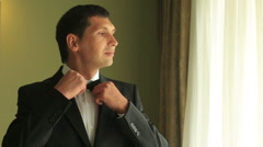 Cool confident relaxed groom adjusting bow tie looking away. Wedding concept - stock footage