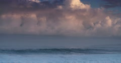 Blue waves roll into the coast of Hawaii in slow motion with pink clouds Stock Footage