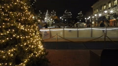 Skaters on ice during christmas at downtown outdoor rink at night Stock Footage