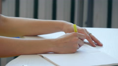 Hand of young girl write on notebook in scholl or colledge Stock Footage