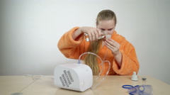 Teenage girl preparing to use a nebulizer for asthma treatment at home Stock Footage