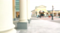 Blurred slender brunette girl in jeans walking with her purchasings by columns Stock Footage
