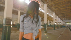 Girl dancing in an abandoned factory in the sun, and the dust raised Stock Footage