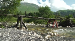 The Wooden Bridge Over the Fast Mountain River Against High Mountains Stock Footage