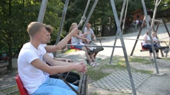 People ride on a swing in the summer park Stock Footage