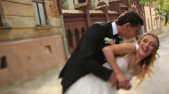 Happy groom spinning and kissing his beautiful blonde bride in front of an Stock Footage