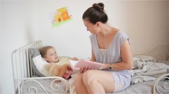 Beautiful Mom reading fairy tales while putting her little daughter to sleep Stock Footage