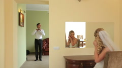 Stylish young groom and bride getting ready for their big day in their Stock Footage