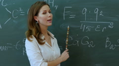 Teacher in the classroom on blackboard background explain something in phisics Stock Footage