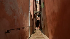 Narrow passage and ochre colored buildings, Roussillon, France, tilt Stock Footage