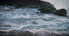 Blue waves roll into the coast of Hawaii in slow motion and break over rocks. Stock Footage