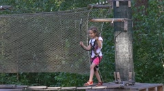Happy Girl is in Adventure Park Walking by Rope Bridge in Summer Day Child Has Stock Footage