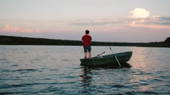 Young man sailing boat on the river and fishing, sunset Stock Footage