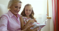Young girl and grandmother watching together photo album, sitting in cozy - stock footage