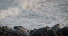 Blue waves roll into the coast of Hawaii in slow motion and break along a craggy Stock Footage