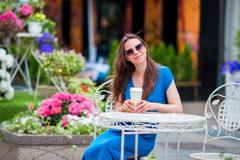Happy young urban woman with modern mobile and coffee at outdoor cafe in Europe Stock Photos