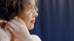 Beautiful girl wears earrings - photosession Stock Footage