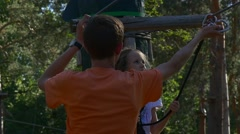 Adult Instructor Corrects the Size of Equipment For Climbing on Trees Stock Footage