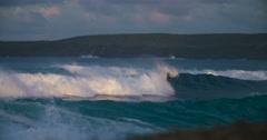 Ocean waves roll into a coastline in golden light in slow motion. Stock Footage