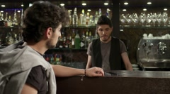 Barman gives a drink to the boy, who is sitting by a bar rack . Stock Footage