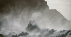 Huge ocean waves roll into a rocky shore in slow motion. Stock Footage