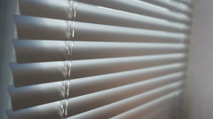 Young man close and open is venetian blinds by the window Stock Footage