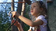 Little Girl Fixing the Climber Fastens Gear Adventure Rope Park in Summer Sunny Stock Footage