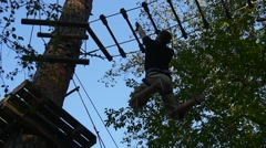 Tourist is Moving by Rope Road on Hands Adventure Park Young Man Has Fun in Stock Footage