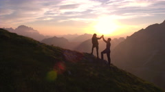 Aerial - Flyover hiking couple celebrating successful climb on the mountain Stock Footage