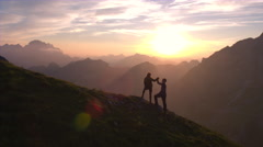 Aerial - Silhouette of a couple giving each other a high five celebrating succes Stock Footage