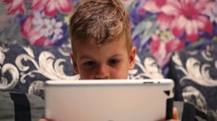 Close-up shot of little boy watching cartoon or movie on touch pad Stock Footage