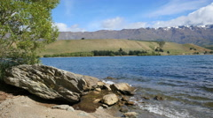 New Zealand Lake Dunstan with big rock and moraine Stock Footage