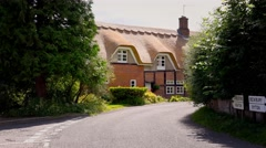 Old English thatched house on country lane Stock Footage